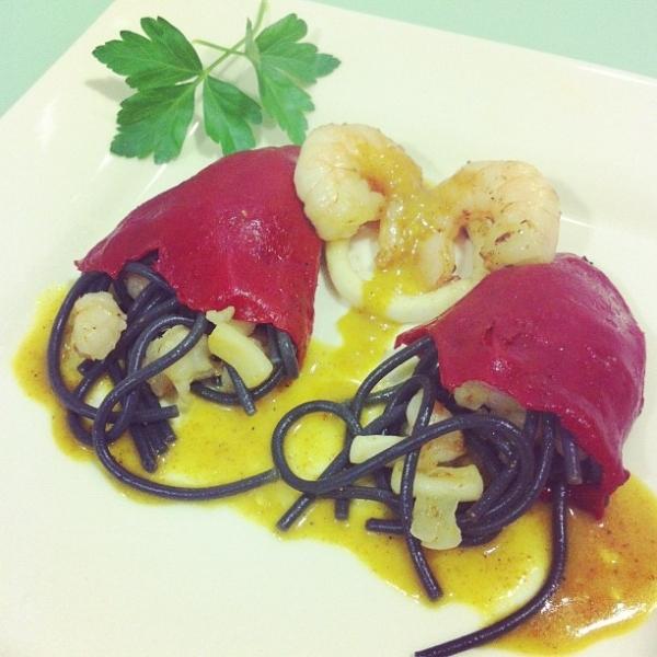 Piquillos rellenos de fideos negros, langostinos y calamares con salsa suave de curry y grana padamo